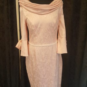 The rose Gold cape dress from the Anoola mother of the bride occasion wear collection is the perfect choice for the contemporary mother of the bride. The beautiful blush fabric glistens with rose gold metallic throughout. The dress boosts a striking stand up collar neckline,and completed with attached short cape .